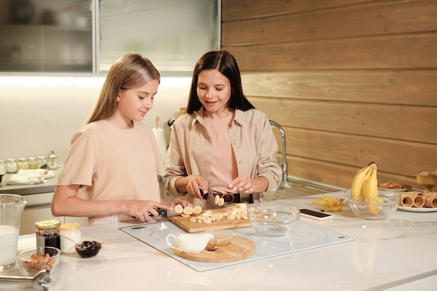 Pretty teenage girl helping her mother cut bananas for homemade icecream while cooking together in the kitchen on weekend