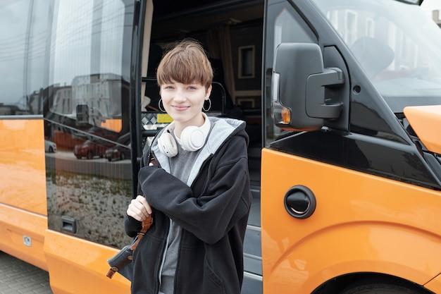 Довольно девочка-подросток в повседневной одежде, глядя на вас перед автобусом
