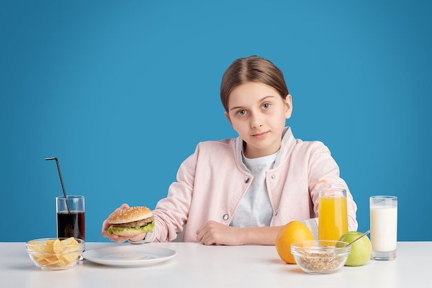 테이블에 앉아 햄버거, 감자 칩을 먹고 콜라를 점심으로 마시는 동안 당신을보고있는 예쁜 십대 소녀