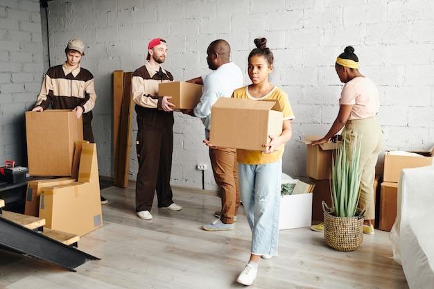 Симпатичная девочка-подросток африканской национальности несет упакованную картонную коробку, помогая отцу и матери переехать в новую квартиру или дом