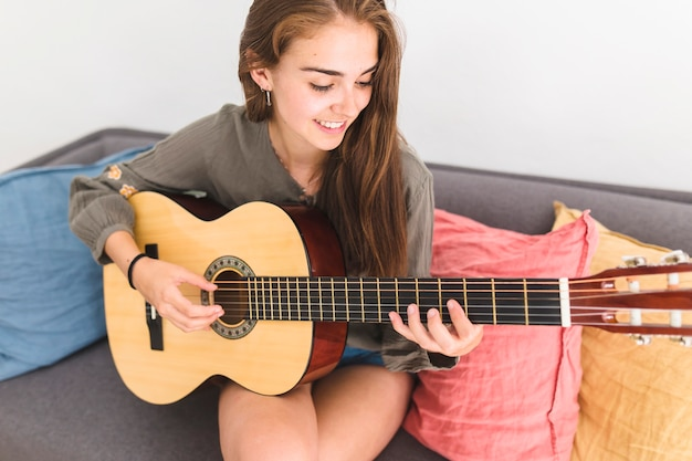 Pretty teenage girl playing guitar at home