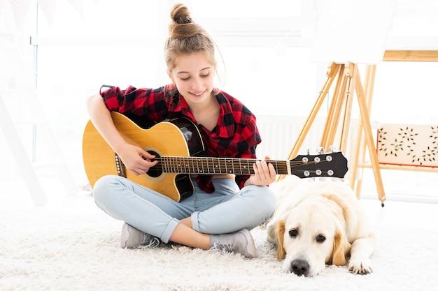 家でかわいい犬の隣でギターを弾くかわいい10代の少女