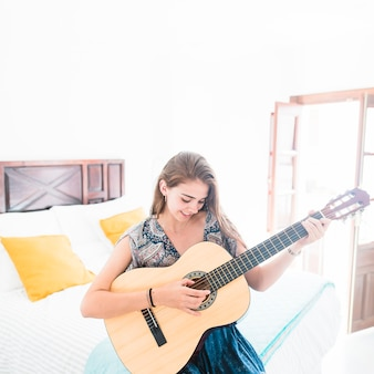 Pretty teenage girl sitting on bed playing guitar