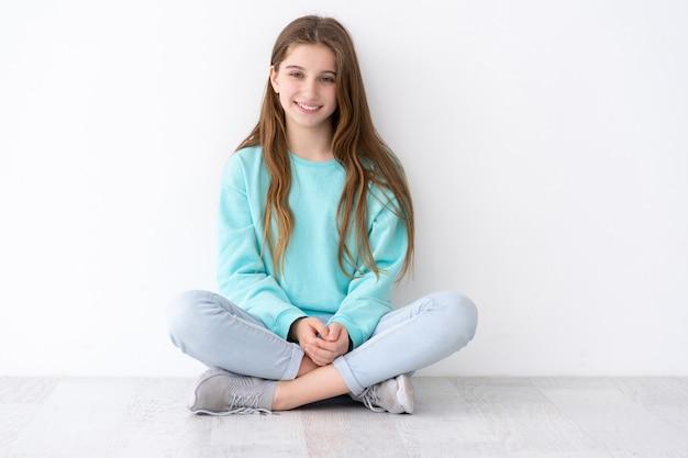 白い壁にもたれて床に座っているかなり 10 代の少女