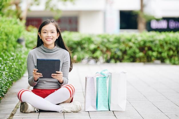 Симпатичная девочка-подросток сидит на тротуаре рядом с хозяйственными сумками, держит планшетный компьютер и улыбается в камеру