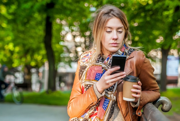 Pretty teenage girl using her mobile phone while sitting on wooden bench. casual style - jeans. making plans. woman using a cellphone while sitting on a bench.