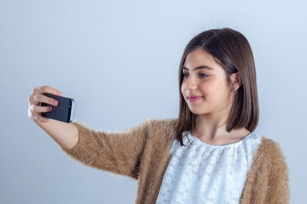 Pretty teenage girl with mobile phone in studio.