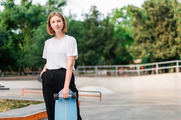 Pretty teenage girl with skateboard in the skate park