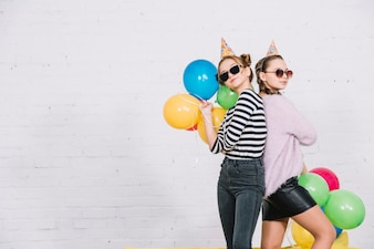 Pretty teenage girls standing back to back holding colorful balloons in hand