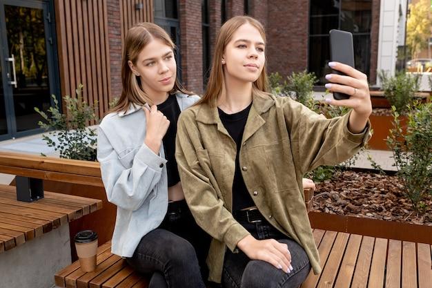 벤치에 앉아있는 동안 셀카를 만드는 예쁜 십대 쌍둥이