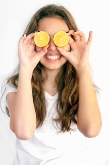 Pretty teenager girl covering her eyes with cut lemons. lemon sunglasses