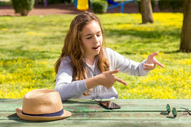Pretty teenager girl emotiomally tells the story at the summer park