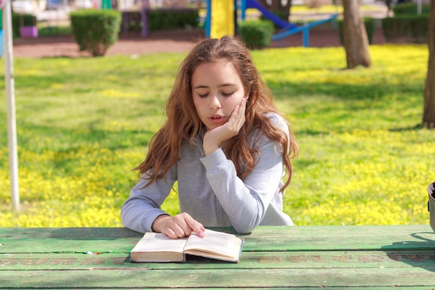 Pretty teenager girl reading a book and studying homework at the summer park