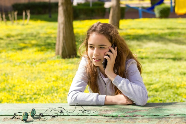 Pretty teenager girl talking by mobile cellpfone smartphone at the summer park