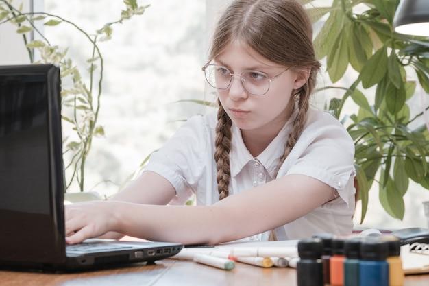 ノートパソコンで入力し、自宅のテーブルの後ろに座って宿題をしているかなりティーンエイジャーの女の子。眼鏡をかけた若い美しい少女、ラップトップでオンライン学習、遠隔教育、独学