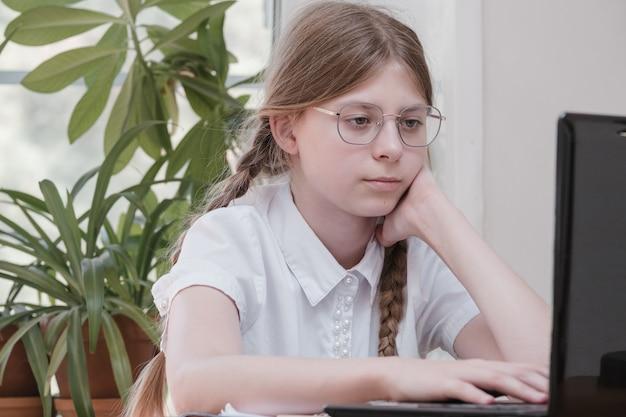 예쁜 10대 소녀가 노트북에 타이핑을 하고 집에서 테이블 뒤에 앉아 숙제를 하고 있습니다. 안경을 쓴 아름다운 소녀, 노트북으로 온라인 학습, 원격 학습, 독학
