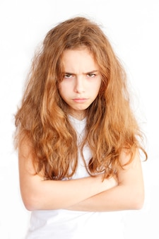 Pretty teenager girl with long hair makes very angry funny face