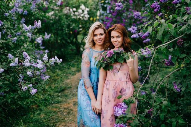 Милые, нежные и веселые сестры-близняшки в красивых платьях позируют вместе в солнечном летнем парке.