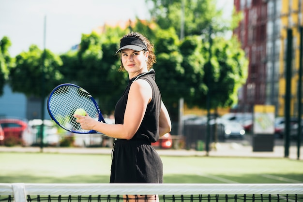 Pretty tennis player hitting ball on a sunny day