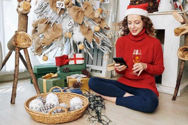 サンタの帽子でかなりテキストメッセージの女性