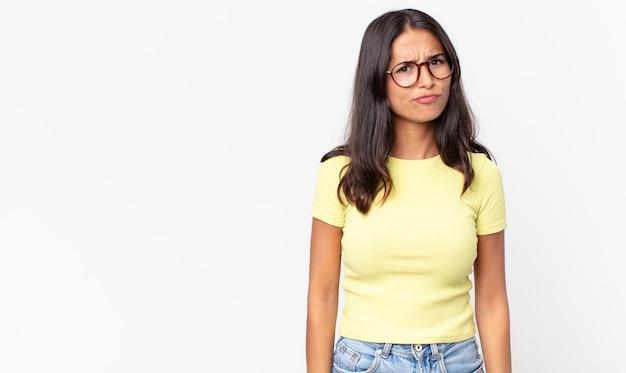 Pretty thin hispanic woman feeling confused and doubtful