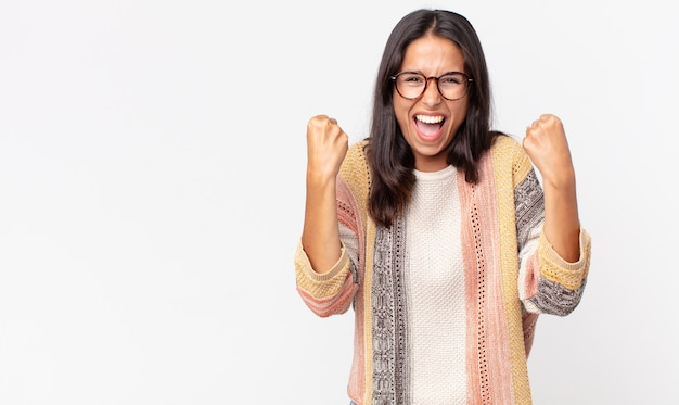 Довольно худая латиноамериканка чувствует себя счастливой, позитивной и успешной, празднует победу