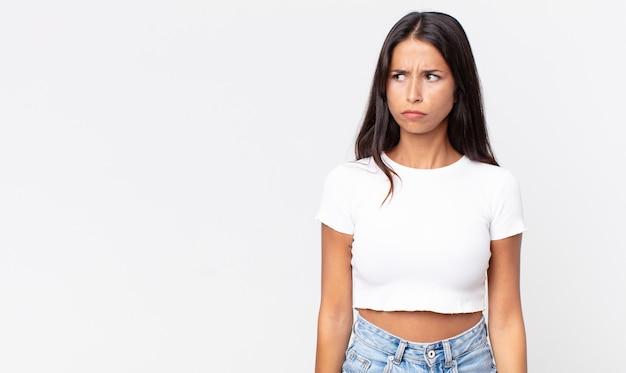 かなり薄いヒスパニック系の女性は、悲しみ、動揺、または怒りを感じ、横を向いています