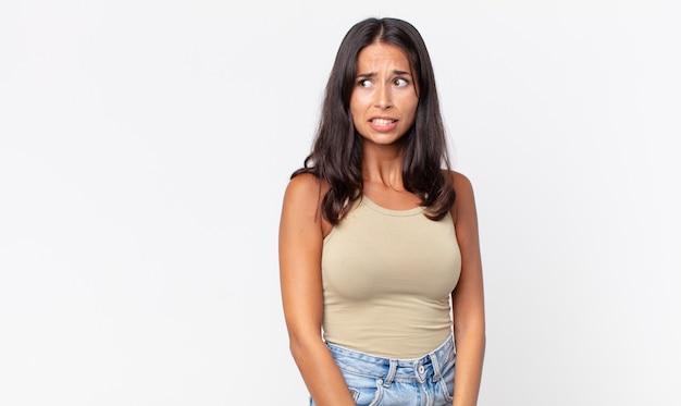 Pretty thin hispanic woman looking worried,panicking and clenching teeth