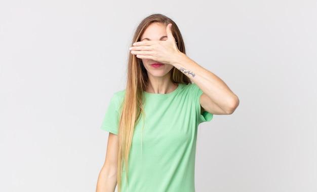 片手で目を覆っているかなり細い女性は、恐怖や不安を感じ、不思議に思ったり、盲目的に驚きを待っています