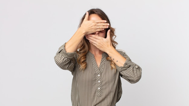 Pretty thin woman covering face with both hands saying no to the camera! refusing pictures or forbidding photos
