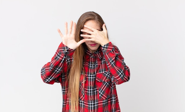 Pretty thin woman covering face with hand and putting other hand up front to stop camera, refusing photos or pictures