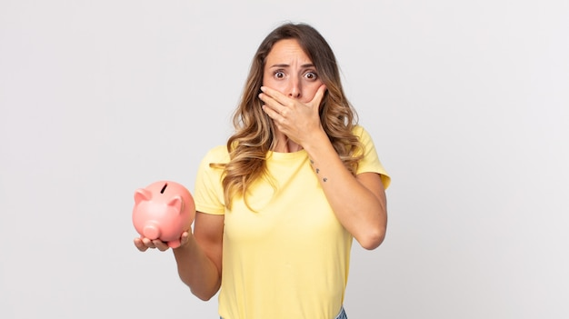Pretty thin woman covering mouth with hands with a shocked and holding a piggybank