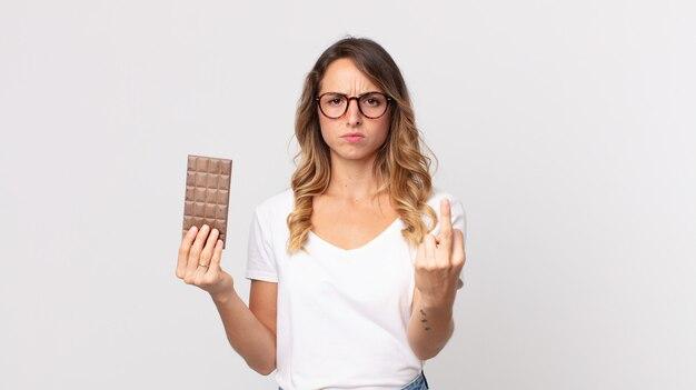 화나고 짜증나고 반항적이고 공격적이며 초콜릿 바를 들고 있는 꽤 마른 여성