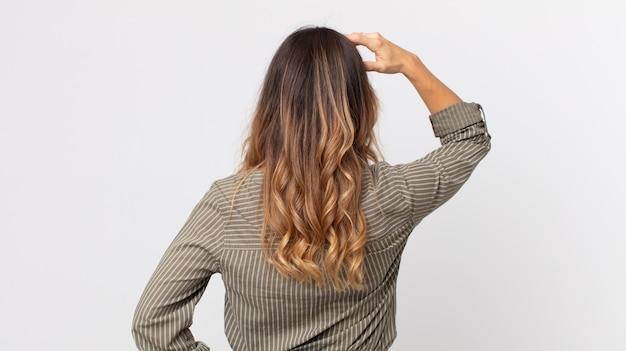 かなり細い女性が無知で混乱していると感じ、解決策を考え、腰に手を、頭に他の手を、背面図
