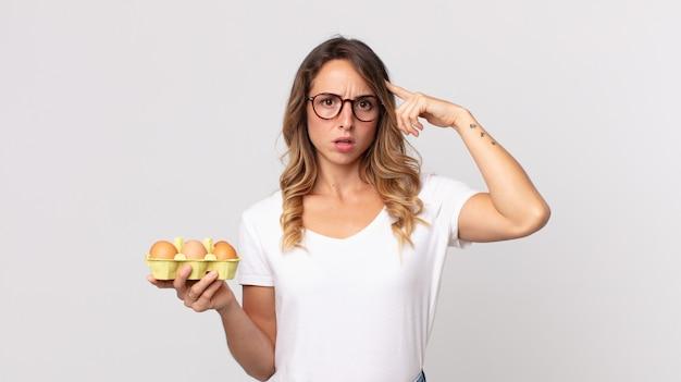 Довольно худая женщина смущена и озадачена, показывая, что вы сумасшедший, и держит коробку с яйцами