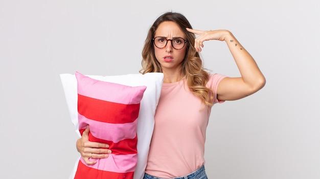 Довольно худая женщина смущена и озадачена, показывая, что вы сошли с ума в пижаме и держите подушку