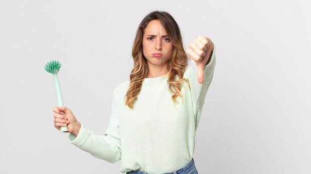 Довольно худая женщина чувствует себя крестно, показывает палец вниз и держит щетку для мытья посуды