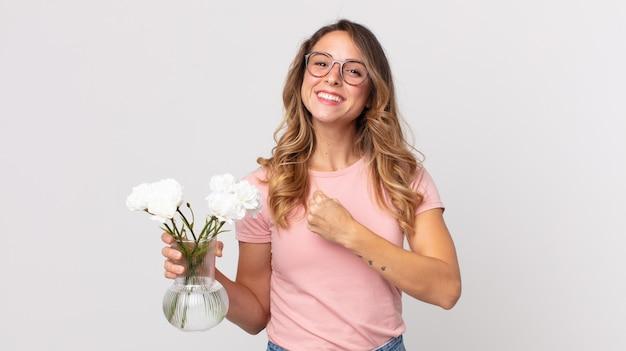 Довольно худая женщина чувствует себя счастливой и сталкивается с проблемой или празднует и держит декоративные цветы
