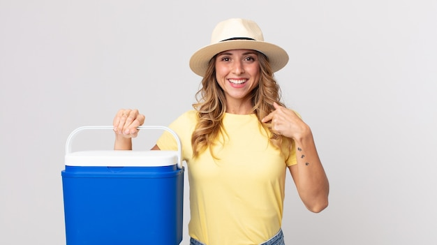 Pretty thin woman feeling happy and pointing to self with an excited and holding a  summer picnic fridge