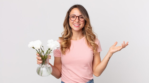 幸せを感じ、解決策やアイデアを実現し、装飾的な花を持って驚いたかなり薄い女性