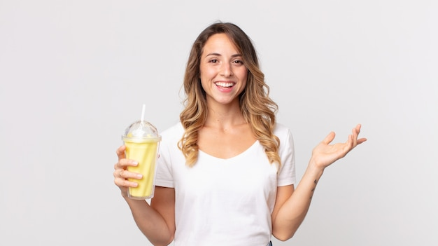 Pretty thin woman feeling happy, surprised realizing a solution or idea and holding a vanilla milkshake
