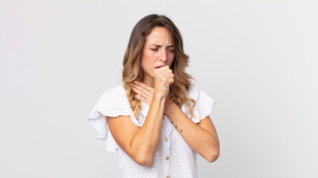 喉の痛みとインフルエンザの症状で気分が悪くなり、口を覆って咳をするかなり細い女性