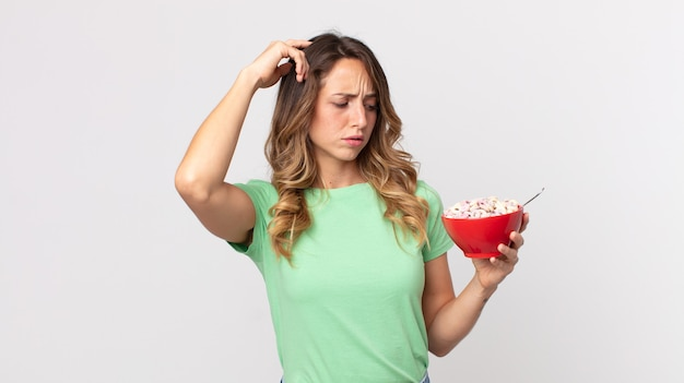 戸惑い、混乱し、頭をかいて、朝食用のボウルを持っているかなり薄い女性
