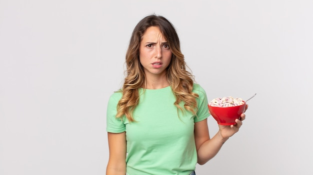 Pretty thin woman feeling puzzled and confused and holding a breakfast bowl