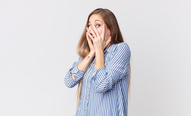 Довольно худая женщина чувствует себя напуганной или смущенной, подглядывает или шпионит глазами, наполовину прикрытыми руками