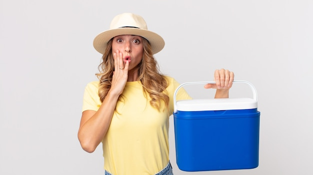 Pretty thin woman feeling shocked and scared and holding a  summer picnic fridge