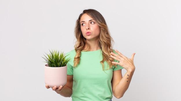 Довольно худая женщина чувствует стресс, тревогу, усталость и разочарование и держит декоративное растение