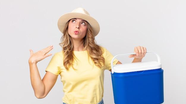 Довольно худая женщина чувствует стресс, тревогу, усталость и разочарование и держит в руках холодильник для летнего пикника