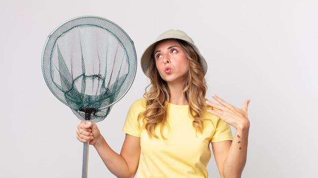 かなり薄い女性は、ストレス、不安、疲れ、欲求不満を感じ、帽子をかぶって魚網を持っています