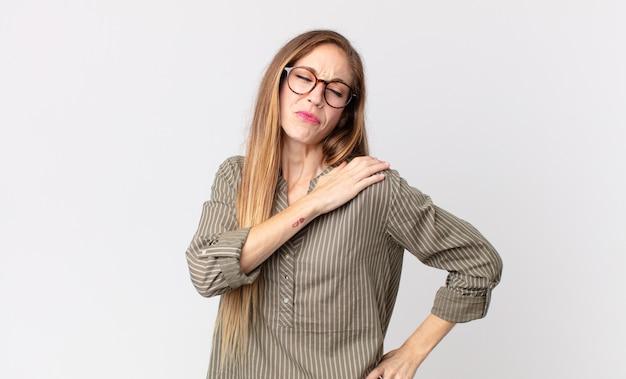 꽤 마른 여성이 피곤하고, 스트레스를 받고, 불안하고, 좌절하고, 우울하고, 허리나 목 통증으로 고통받고 있습니다.